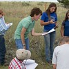 Kim Dolatta, of the U.S. Forest Service, helps youth with plant identification near the Chadron State College Rangeland Complex during a July 12, 2017, Nebraska Extension workshop. (Photo by Tena L. Cook/Chadron State College)