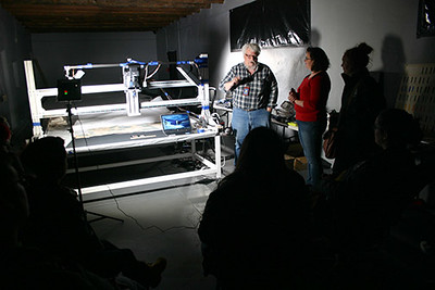 Mark Mackenzie, center, explains a high tech camera and lighting system that uses multiple spectra of light to uncover layers of paint, minerals or cotton fibers on an animal hide in the New Mexico History Museum. Sarah Polak, director of the Mari Sandoz High Plains Heritage Center, right, and Chadron State College students look on during a tour in March 2017. (Courtesy photo)