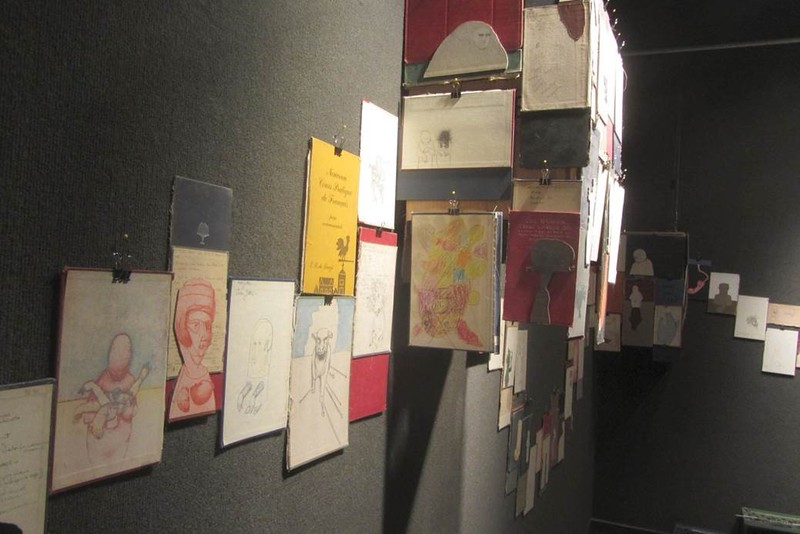 Parts of old books, including covers and individual pages, some with drawings added by previous owners or readers, are mounted in undulating shapes on the walls of Memorial Hall's Main Gallery in the art installation by Todd Christensen on display through Nov. 13, 2015. (Photo by George Ledbetter)