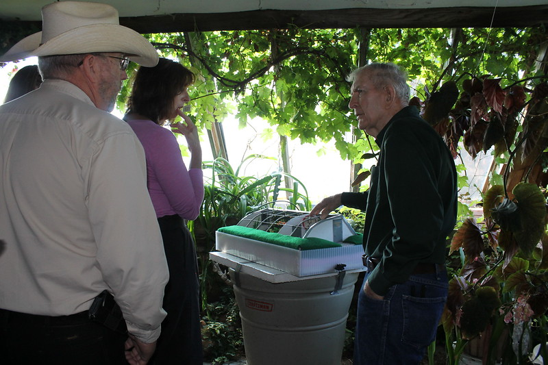 Russ Finch, right, uses a model to explain his new greenhouse design to members of the Alliance business community Kevin Howard, left, and Holly Heath, center. (Photo by Kellie Aye, NBDC graduate assistant)