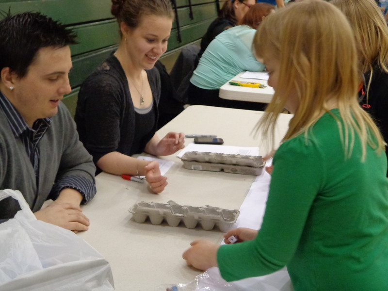 Chadron State College students from left, Tate Acton of Mitchell, Nebraska, and Rachel Swamy of North Bend, Washington, help Laney Smith at the 2013 Family Math Night in Hay Springs. (Courtesy photo)