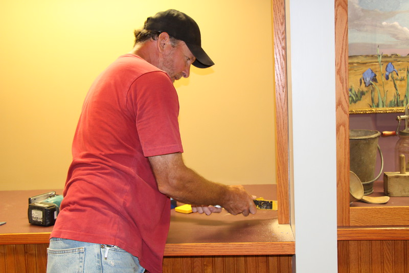 Kent Wickham works on one of two C.F. Coffee Gallery exhibits in the Mari Sandoz High Plains Center being renovated this summer. (Tena L. Cook/CSC)
