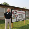 Chris Singpiel, Admissions and Military and Veteran Services Coordinator, stands in front of the newly re-purposed West Court #26 unit which now houses the Military/Veteran Service Center. (Photo by Tena L. Cook./CSC)