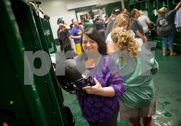 Stacey Chiasson takes her son Robbie's football helmet from his locker inside the football field house Wednesday Aug. 26, 2015 so she can decorate it with school decals for the team's first game Friday night. The Chiasson family evacuated to Tyler during Hurricane Katrina 10 years ago this week.  (Sarah A. Miller/Tyler Morning Telegraph)