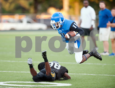 John Tyler's Kieran Freeman (11) is tripped up by a Mount Pleasant player during a scrimmage Friday night at John Tyler High School.  (Sarah A. Miller/Tyler Morning Telegraph)
