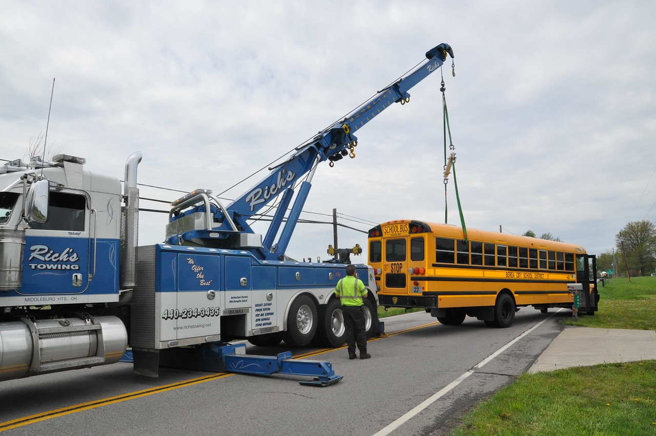 ASHLEY FOX / GAZETTE A tow truck operator works on getting a school bus aligned to hook up to a tow truck Tuesday morning.