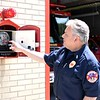 ADAM SHANKS — THE BERKSHIRE EAGLE<br /> North Adams Fire Lt. John Paciorek demostrates how one of the city's old fire alarm call boxes worked. As of Tuesday, the city has officially transitioned to a radio-based system, replacing the old telegraph boxes.