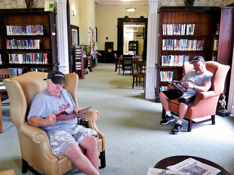 Paul LaForest (left) and Guy Tassone (right) enjoy two of the four new chairs donated by the Friends of the North Adams Public Library for the library's reading room. The neaby coffee table was a gift from Drury High School Class of 1962. (Jennifer Huberdeau/North Adams Transcript)