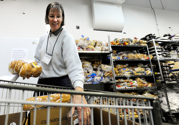 """Volunteer Carolynn Keefner places food into a shopping cart for a client on Tuesday, March 13, at the North Denver Cares Food Pantry at 6900 West 117th Avenue in Broomfield. For more photos and video of the food pantry go to  <a href=""""http://www.dailycamera.com"""">http://www.dailycamera.com</a><br /> Jeremy Papasso/ Camera"""