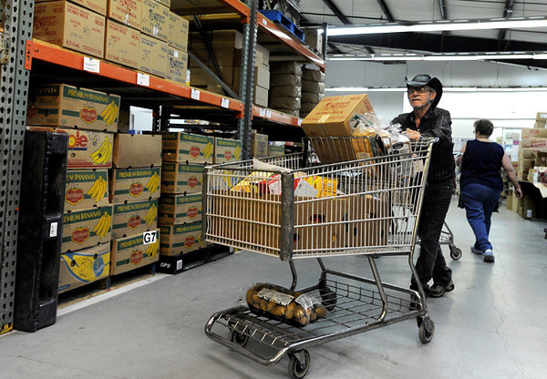 "Volunteer Don McLaughlin pushes a shopping cart full of food for a client on Tuesday, March 13, at the North Denver Cares Food Pantry at 6900 West 117th Avenue in Broomfield. For more photos and video of the food pantry go to  <a href=""http://www.dailycamera.com"">http://www.dailycamera.com</a><br /> Jeremy Papasso/ Camera"
