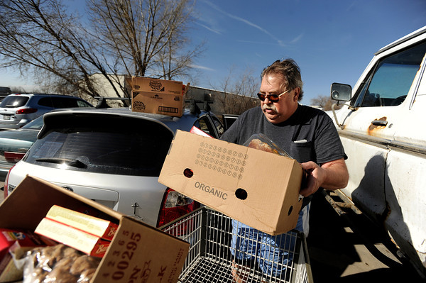 "Don Clochko, of Broomfield, loads his shopping cart of food into his car on Tuesday, March 13, at the North Denver Cares Food Pantry at 6900 West 117th Avenue in Broomfield. For more photos and video of the food pantry go to  <a href=""http://www.dailycamera.com"">http://www.dailycamera.com</a><br /> Jeremy Papasso/ Camera"
