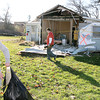 Reporter photo by Rod Rose<br /> Aaron Matheny, once of several volunteers from Centenary United Methodist Chuch,  stuffs debris in a garbage back in a south-side Lebanon neighborhood devastated by a tornado Sunday.