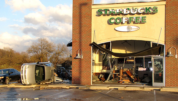 Reporter photo by Rod Rose<br /> A small car rests next to the Starbucks coffee shop on South Lebanon Street where it was tossed by a tornado Sunday afternoon. Although the building's interior was shredded, no one was injured.