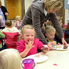 Ellison Smith enjoys her bite of cupcake while Heather Beaupre helps her son Matthew decorate a cupcake Friday morning, Oct. 25, at Hussey-Mayfield Memorial Public Library. Children listened to a short story and were able to decorate their own cupcakes by mixing different colors of frosting.