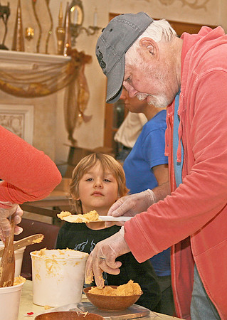 "BALLERS<br /> Elizabeth Pearl | The Lebanon Reporter<br /> SAY CHEESE: Grayson Forrester, five, watches as Tony Reynolds scoops and measures out 11 ounce bowls of smoked cheddar cheese. The cheese is then rolled in pecan and parsley and refridgerated for the annual Symphony at Sunset cheese ball fundraiser. A group of volunteers gathered Sunday and Monday to prepare 1,800 of the treats, using 680 pounds of bleu and cheddar cheese. Proceeds from the $8 cheese balls goes to fund the annual Indianapolis Sympony Orchestra concert before the Fourth of July, and to sponsor local fifth-grade students on a trip to the Hilbert Circle Theatre. <br /> The organization is always looking for volunteers to help with the hours of weighing, rolling and bagging required to make the cheese balls, said Symphony at Sunset President Lori French. <br /> ""It's nice to get together,"" she said. ""Because we lost volunteers we've been asking friends, and Tri Kappa is here. People that have been in the group come back and help and we have a good time and catch up.""<br /> The cheese balls are available for purchase at the Cutting Edge Salon, 115 E. Main St., Lebanon. They can also be purchased by request on the Symphony at Sunset Facebook or Twitter page, or by calling 317-440-3567."