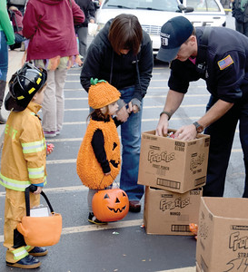 Miniature firefighter Luke Myer, 4, and his jack-o-lantern sister, Ruthie, 2, shyly accept treats from Zionsville firefighter Matt Coyner at the Boone Village Halloween Party. The Zionsville children attended with their grandmother, Ginny Myer, of Cincinnati, who was in town visiting a new grandbaby and celebrating Ruthie's birthday.