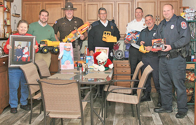 Elizabeth Pearl | The Lebanon Reporter ANNUAL CAMPAIGN KICKS OFF: From left, Janet Smith -- holding a picture of her mother, Myrtle Bailey, along with Lebanon Mayor Matt Gentry, Boone County Sheriff Mike Nielsen, Zionsville Fire Chief James VanGorder, Lebanon Fire Chief Chuck Batts, Lebanon Police Chief Tyson Warmoth and Lebanon Police Department Major Brad Bailey helped start the annual toy drive.