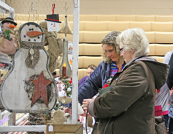 GETTING CRAFTY<br /> Elizabeth Pearl | The Lebanon Reporter<br /> HOLIDAY TRINKETS: Susan Richardson and Carol Anderson look at Christmas-themed crafts Saturday at the Boone County Extension Homemakers' annual Holiday Bazaar. The bazaar was held in the Witham Pavilion and the East Pavilion at the Boone County 4-H Fairgrounds. Dozens of vendors sold holiday decorations, gifts, books and treats from the two buildings, while Mrs. Clause passed out candy canes and posed for photos.
