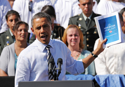 President Barack Obama holds up his American Jobs Act bill, Tuesday Sept. 27, 2011, during his speech at Lincoln High School.  RJ Sangosti, The Denver Post