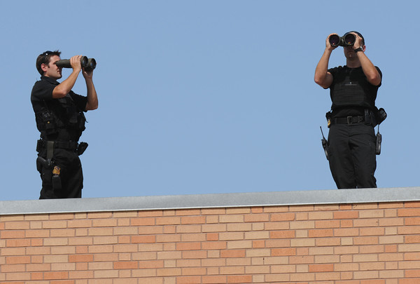 Security on the roof of Lincoln High School keeps an eye on the crowd as people start to show, Tuesday Sept. 27, 2011, for President Barack Obama's speech at the Denver school.  RJ Sangosti, The Denver Post