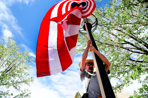 "Joe Eskew pulls down his American Flag from a pole outside the Boulder County Courthouse during the Occupy Boulder American Spring Rally in downtown Boulder on Saturday March 31, 2012.<br /> For more photos and a video of the march and rally go to  <a href=""http://www.dailycamera.com"">http://www.dailycamera.com</a><br /> Photo by Paul Aiken"