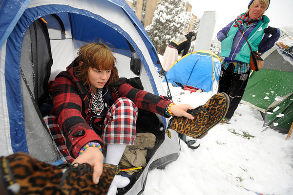 """Emily Porman knocks the snow from her boots as she gets into her tent at the Occupy Boulder encampement in front of the Boulder County Courthouse on the Pearl Street Mall in Boulder on Thursday December 1, 2011. Eva Kirk is seen in the background. <br /> For more photos and a video from the site go to  <a href=""""http://www.dailycamera.com"""">http://www.dailycamera.com</a><br /> Photo by Paul Aiken The Camera"""