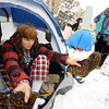 "Emily Porman knocks the snow from her boots as she gets into her tent at the Occupy Boulder encampement in front of the Boulder County Courthouse on the Pearl Street Mall in Boulder on Thursday December 1, 2011. Eva Kirk is seen in the background. <br /> For more photos and a video from the site go to  <a href=""http://www.dailycamera.com"">http://www.dailycamera.com</a><br /> Photo by Paul Aiken The Camera"