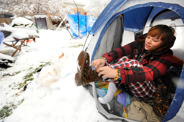 """Emily Porman takes off her snowy boots as she gets into her tent at the Occupy Boulder encampement in front of the Boulder County Courthouse on the Pearl Street Mall in Boulder on Thursday December 1, 2011. <br /> For more photos and a video from the site go to  <a href=""""http://www.dailycamera.com"""">http://www.dailycamera.com</a><br /> Photo by Paul Aiken The Camera"""