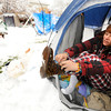 "Emily Porman takes off her snowy boots as she gets into her tent at the Occupy Boulder encampement in front of the Boulder County Courthouse on the Pearl Street Mall in Boulder on Thursday December 1, 2011. <br /> For more photos and a video from the site go to  <a href=""http://www.dailycamera.com"">http://www.dailycamera.com</a><br /> Photo by Paul Aiken The Camera"