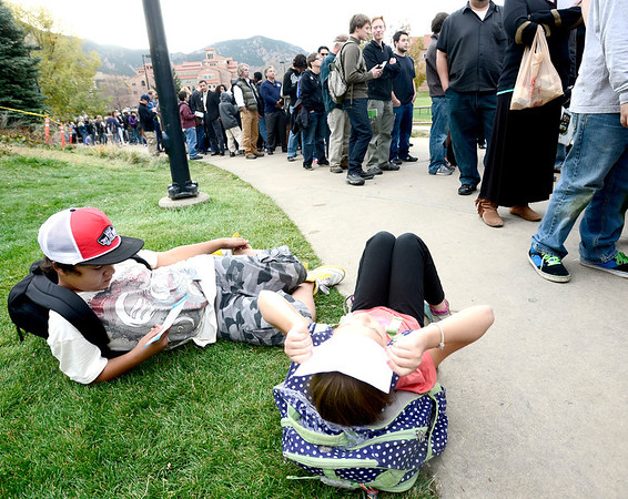 Kai Willett (left), 11,  and India Willett (right), 9, rest in the grass while waiting in line to see President Barak Obama at the University Colorado in Boulder, Colorado November 1, 2012.  DAILY CAMERA/ MARK LEFFINGWELL