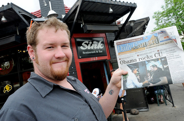 """Dan Williams holds up yesterday's Daily Camera with the photo of himself shaking the hand of President Barack Obama during his visit to The Sink on The Hill.<br /> For more photos and a video of the sink, go to  <a href=""""http://www.dailycamera.com"""">http://www.dailycamera.com</a>.<br /> Cliff Grassmick / April 25, 2012"""