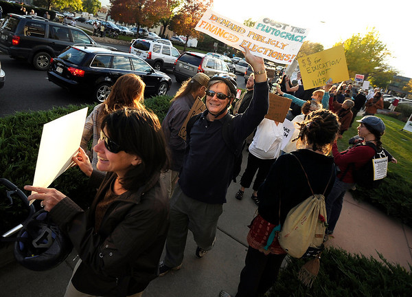 "Kate Paradis, of Boulder, left, and her husband David, middle, walk through the crowd with their protest signs on Friday, Oct. 14, during the ""Occupy Boulder"" rally near the intersection of Canyon Boulevard and 26th Street in Boulder. For more photos of the rally go to  <a href=""http://www.dailycamera.com"">http://www.dailycamera.com</a><br /> Jeremy Papasso/ Camera"