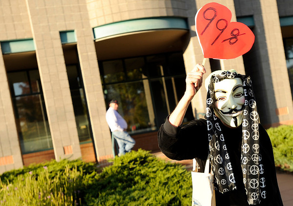 "A woman, name not given, wears a mask and holds a 99 percent protest sign on Friday, Oct. 14, during the ""Occupy Boulder"" rally near the intersection of Canyon Boulevard and 26th Street in Boulder. For more photos of the rally go to  <a href=""http://www.dailycamera.com"">http://www.dailycamera.com</a><br /> Jeremy Papasso/ Camera"