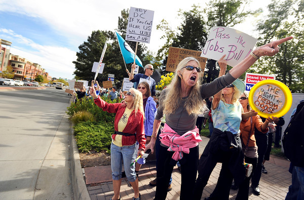 "An angry protester, who refused to give her name, screams loudly while pointing at passing cars on Saturday, Oct. 15, during the ""Occupy Boulder"" rally near the intersection of Canyon Boulevard and Broadway in Boulder. For more photos and a video of the rally go to  <a href=""http://www.dailycamera.com"">http://www.dailycamera.com</a><br /> Jeremy Papasso/ Camera"