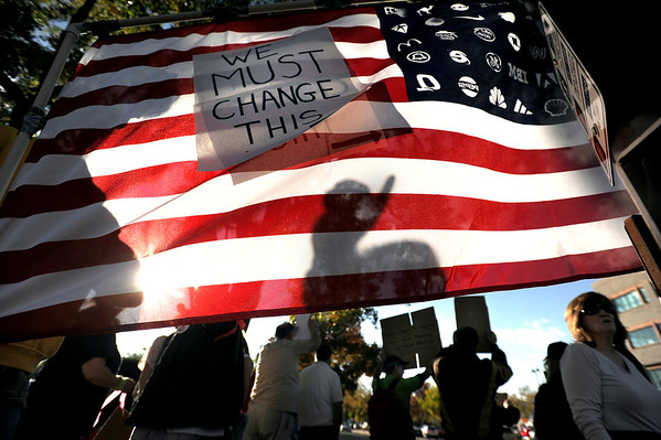 """An american flag with a rally message glistens in the sun on Friday, Oct. 14, during the """"Occupy Boulder"""" rally near the intersection of Canyon Boulevard and 26th Street in Boulder. For more photos of the rally go to  <a href=""""http://www.dailycamera.com"""">http://www.dailycamera.com</a><br /> Jeremy Papasso/ Camera"""