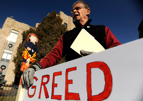 "Tom deMers, of Longmont, holds a rally sign as he listens to people speak during an Occupy Boulder Rally on Saturday, Dec. 10, in downtown Boulder. For more photos and video of the rally go to  <a href=""http://www.dailycamera.com"">http://www.dailycamera.com</a><br /> Jeremy Papasso/ Camera"