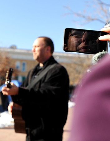 """Elicia Arwen, of Boulder, is reflected in her cell phone while recording a man playing an Occupy Boulder song on his guitar during an Occupy Boulder Rally on Saturday, Dec. 10, in downtown Boulder. For more photos and video of the rally go to  <a href=""""http://www.dailycamera.com"""">http://www.dailycamera.com</a><br /> Jeremy Papasso/ Camera"""