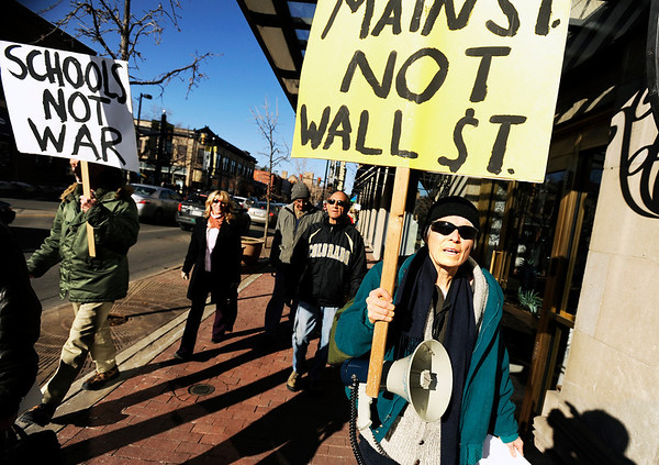"""Carolyn Bninski, of Boulder, right, marches with a rally sign during an Occupy Boulder Rally on Saturday, Dec. 10, in downtown Boulder. For more photos and video of the rally go to  <a href=""""http://www.dailycamera.com"""">http://www.dailycamera.com</a><br /> Jeremy Papasso/ Camera"""
