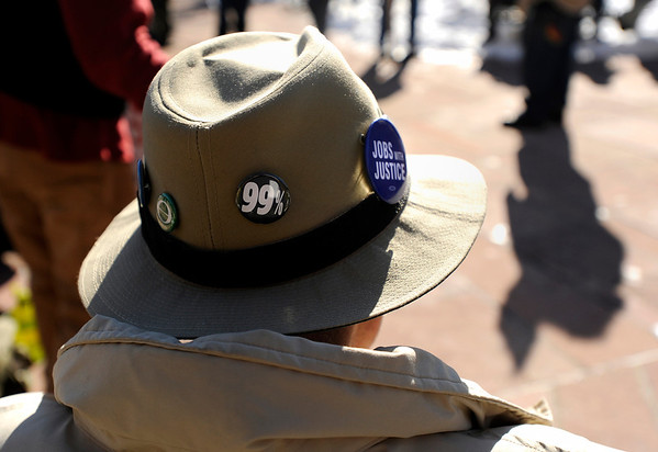"""A man wearing a 99% pin on his hat sits on a bench during an Occupy Boulder Rally on Saturday, Dec. 10, in downtown Boulder. For more photos and video of the rally go to  <a href=""""http://www.dailycamera.com"""">http://www.dailycamera.com</a><br /> Jeremy Papasso/ Camera"""
