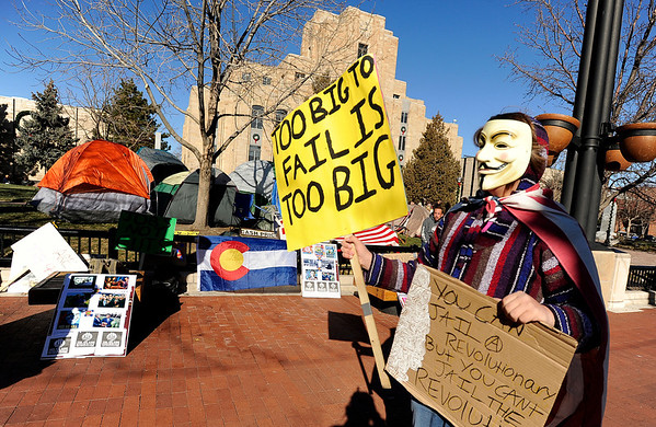 """Sean Malcolm, 15, of Boulder, walks down Pearl Street with his signs during an Occupy Boulder rally on Saturday, Nov. 26, in front of the Boulder County Courthouse on the Pearl Street Mall in Boulder. For more photos and video of the rally go to  <a href=""""http://www.dailycamera.com"""">http://www.dailycamera.com</a><br /> Jeremy Papasso/ Camera"""