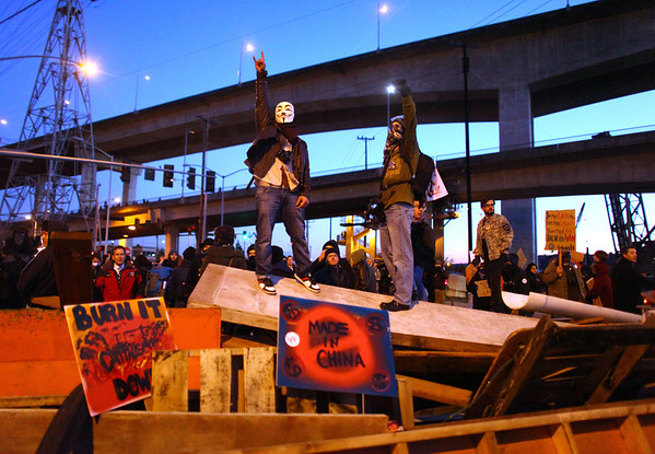 Occupy Ports Seattle.JP(2).JPG Occupy Seattle protesters stand atop a barricade on Monday, Dec. 12, 2011 in  Seattle. Hundreds of anti-Wall Street protesters gathered at the port and tried to shut down operations.  (AP Photo/seattlepi.com, Joshua Trujillo)