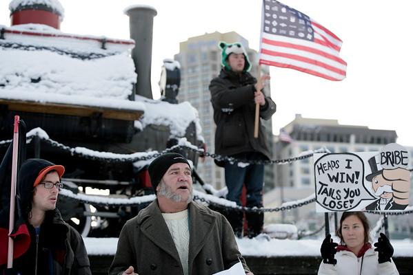 Occupy Ports.JPEG-0ac6c.JPG Brian MacMillan, second left, reads a fake resignation letter from Port of Anchorage director Bill Sheffield in front of the Integrated Concepts & Research Corporation (ICRC) office near the Port of Anchorage, Alaska on Monday, Dec. 12, 2011. ICRC is a major contractor on the Port of Anchorage expansion, a project which Occupy Anchorage claims has been mismanaged and wasteful. The protesters joined other West Coast anti-Wall Street protesters in taking a stand against problems at ports. (AP Photo/Loren Holmes)