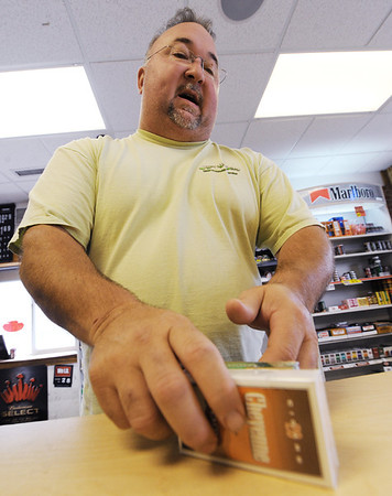 Globe/T. Rob Brown<br /> Tony Perry, owner of Cigs & Suds, sells a couple cigarette packs to a customer Monday morning at the Webb City business on Madison.