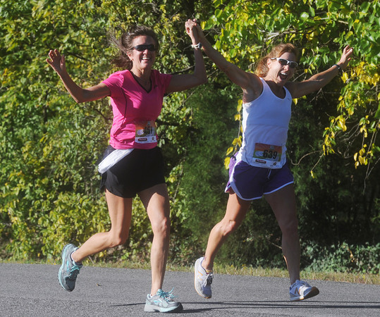 Globe/Roger Nomer<br /> Theresa Dorrell, Greeley, Kan., left, and Bianca Williams, Shawnee, Kan., respond to the crowd as they approach the finish line of the half marathon during Sunday's Mother Road Marathon.