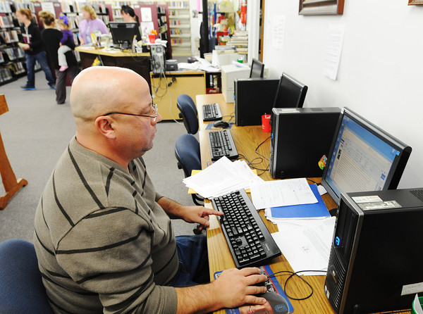 Globe/T. Rob Brown<br /> Paul Vickers of Seneca uses the library's computers and Internet access to research his disability case Thursday morning, Oct. 25, 2012, in Seneca.