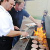 Globe/T. Rob Brown<br /> Pittsburg, Kan., Fire Chief Scott Crain, left, and City Manager Daron Hall kick up the heat as they grill hamburger patties for the Badges & Burgers annual fall fundraiser event for the United Way on Wednesday afternoon, Oct. 17, 2012. Both the Pittsburg Fire and Police departments were involved in preparing and serving the food and beverages.