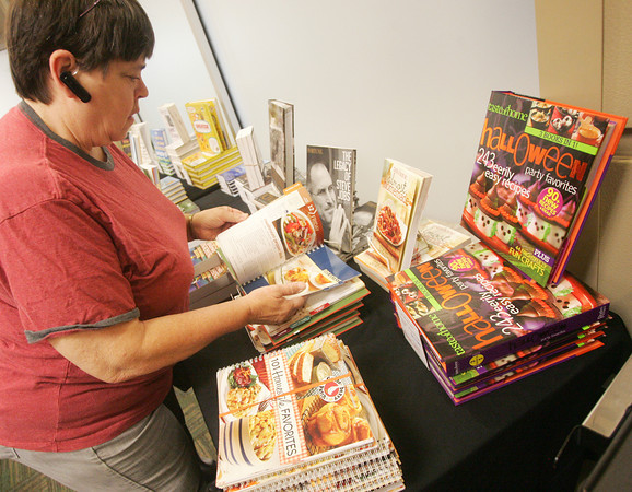 Globe/Roger Nomer<br /> Julia Eichman, adjunct faculty in biology at Missouri Southern, looks over a cookbook at the Books are Fun book fair and Billingsly Student Center on Tuesday morning.  Proceeds from the fair go to help United Way.