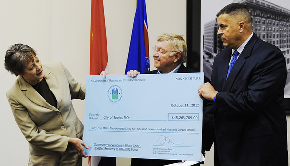 Globe/T. Rob Brown<br /> Theresa Porter, left, deputy regional administrator for Region 7 for the Department of Housing and Urban Department, presents a check for more than $45 million in grant funds to the city of Joplin Thursday morning, Oct. 11, 2012. Accepting on behalf of the city are Mayor Pro-tem Bill Scearce, center, and City Manager Mark Rohr.