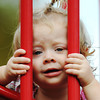 Globe/T. Rob Brown<br /> Nineteen-month-old Emma Cameron, plays peek-a-boo between playground equipment bars with her father, Charlie Cameron, while on an outing Friday afternoon, Oct. 12, 2012, to Landreth Park with her father and mother, Leah Cameron, all of Joplin.