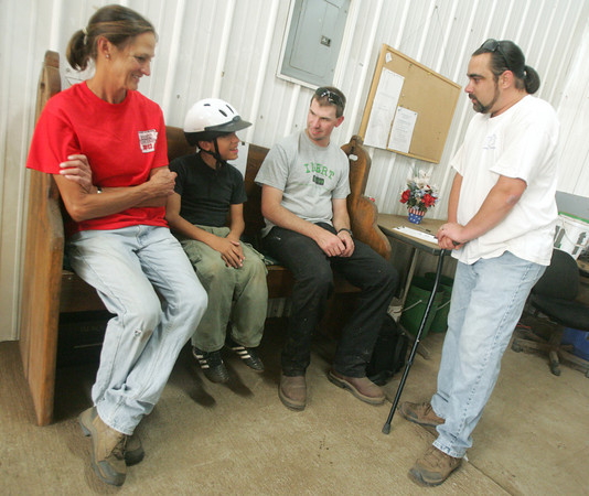 Globe/Roger Nomer<br /> John Brummet talks with rider Isaac Ramirez, 12, and volunteers Mary Jean Hockman and Eric Ginter before class on Wednesday.